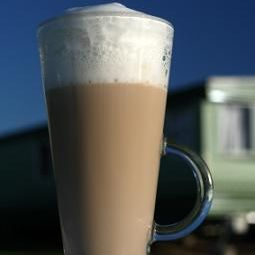 Cafe Latte in a tall glass and deep blue sky